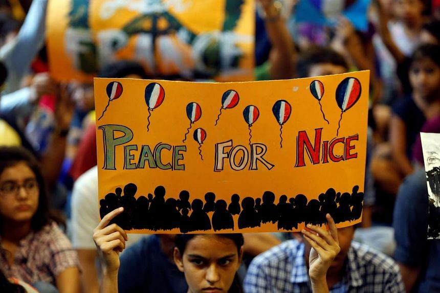 A girl holds up a placard during a prayer meet to show solidarity with the victims of the Bastille Day truck attack in Nice, at a school in Ahmedabad, India, ON July 15, 2016.
