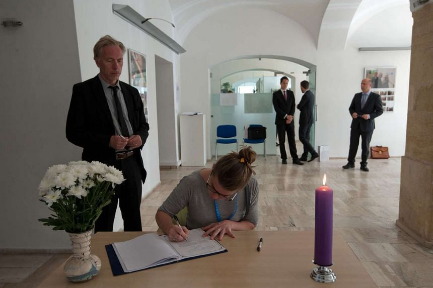 A woman writes in a condolence book at the French embassy in Bratislava, on July 15, 2016, to commemorate the victims of the deadly attacks in Nice.