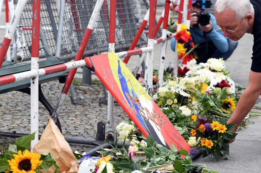 A man places a bouquet of flowers in front of a barricade at the French Embassy in Berlin, Germany, on July 15, 2016.