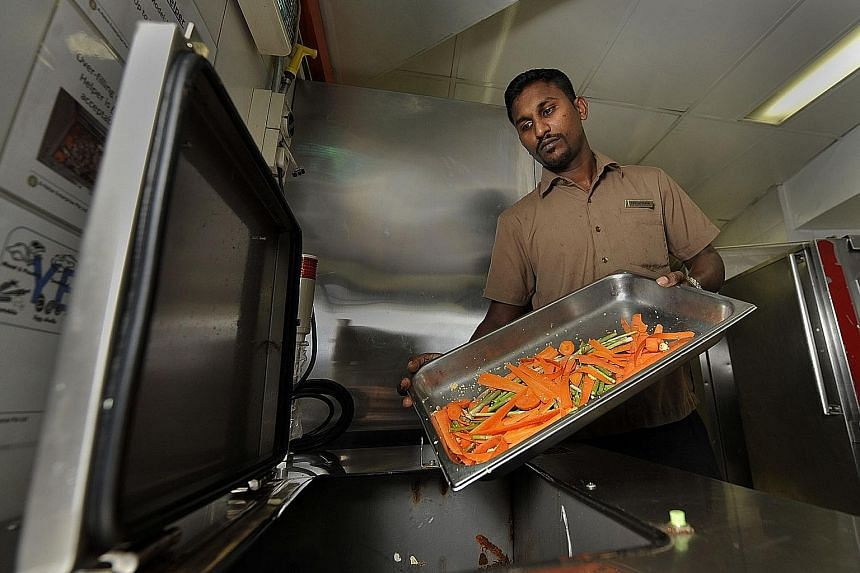 A steward at Fairmont Singapore putting food scraps into a machine that converts solid food waste into fertilisers and liquids in 2012.