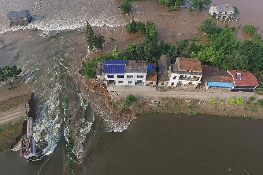 Houses are flooded as a dyke is breached this week in Huarong County, in Hunan Province, on the southern bank of the Yangtze River. Water levels in the middle and lower reaches of great river are falling, but most remain above warning levels.