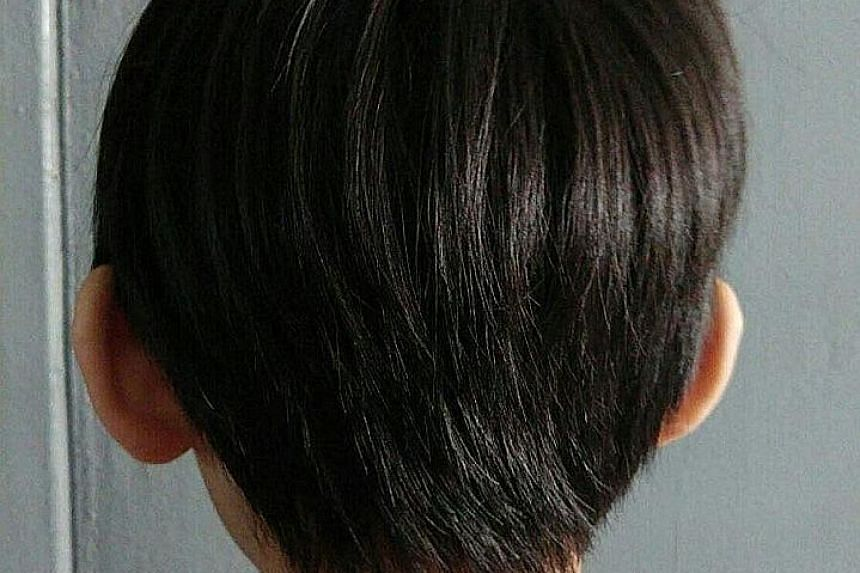 """A back view of the six-year-old involved in the incident. His teacher found his hair too long and clipped it with a girl's hair clip. The incident came to light after another teacher noticed his """"abnormal and despondent"""" behaviour, his father said in"""