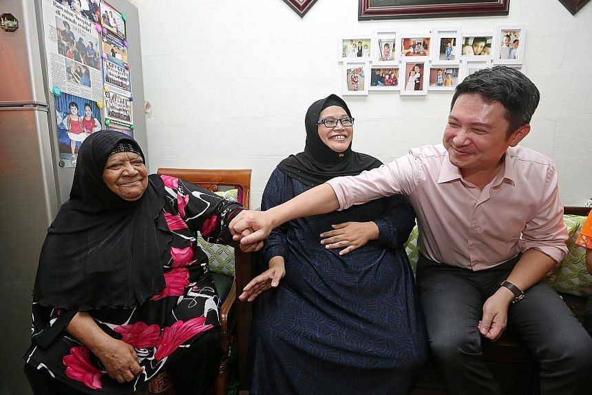 Nee Soon GRC MP Henry Kwek with residents Madam Salmah Kawana (left), 65, and her daughter, Madam Izam Zamah. He and volunteers distributed food yesterday as part of the Kebun Baru Cares programme.