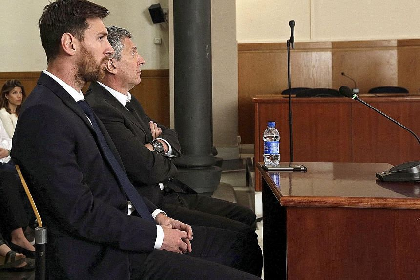 Barcelona's Lionel Messi (foreground) and his father Jorge attending a session of their tax fraud trial last month. They were sentenced to 21 months in prison last week, which prompted the club to start an online solidarity campaign in support of the