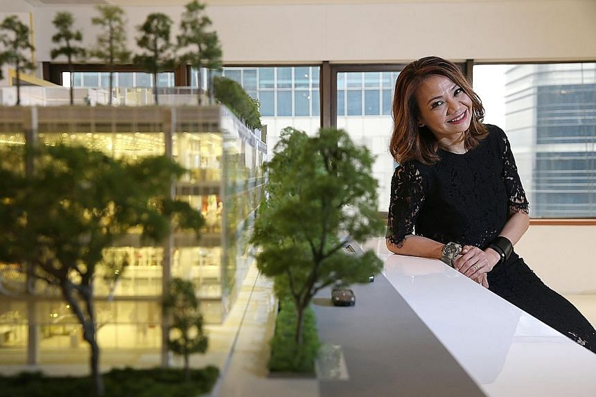 "OUE's Ms Tan, seen here next to a model of OUE Downtown, says that besides a ""social kitchen"", the Downtown Gallery mall will feature an auto deli where people order food using their mobile devices and have it delivered to lockers there."