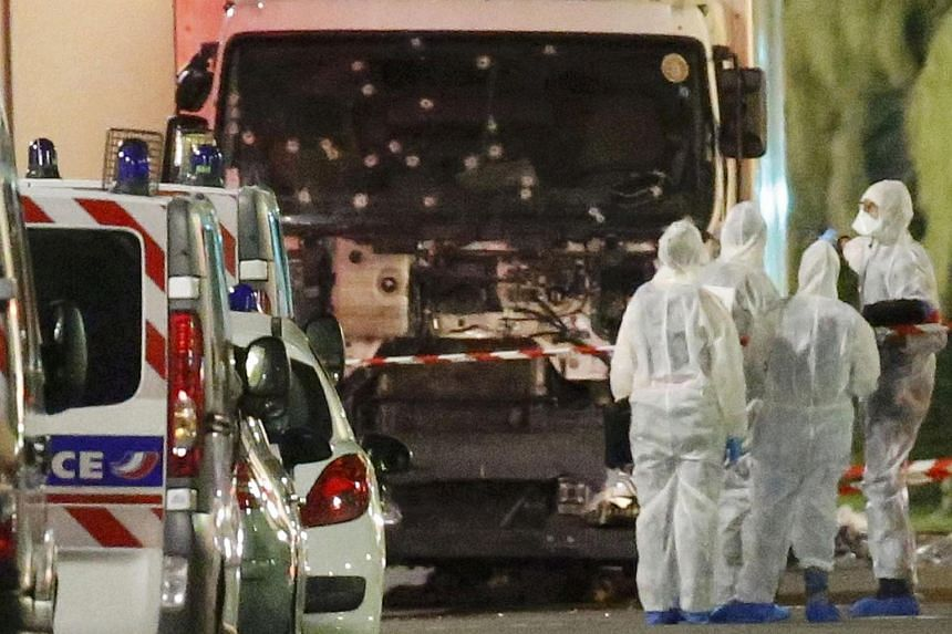 French police forces and forensic officers stand next to a truck on July 15 that ran into a crowd celebrating the Bastille Day national holiday on the Promenade des Anglais killing several people in Nice, France, on July 14.