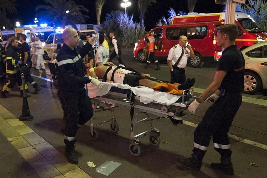 Wounded people are evacuated by emergency teams from the scene where a truck crashed into the crowd during the Bastille Day celebrations in Nice, France on July 14.