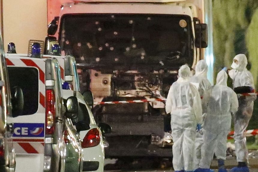 French police and forensic officers stand next to the truck that ploughed into the crowd on the Promenade des Anglais.