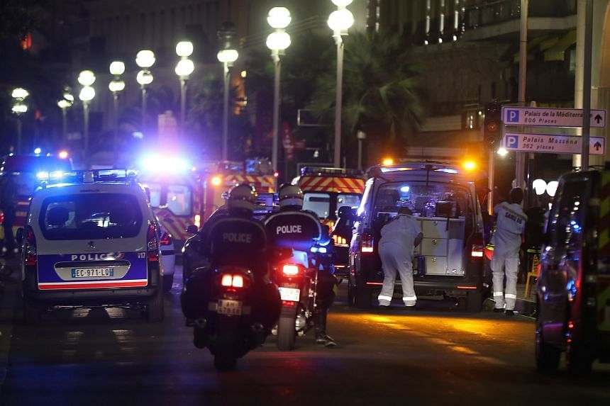 Police officers and rescue workers arrive at the scene of an attack on July 14, after a van ploughed into a crowd leaving a fireworks display in the French Riviera town of Nice.