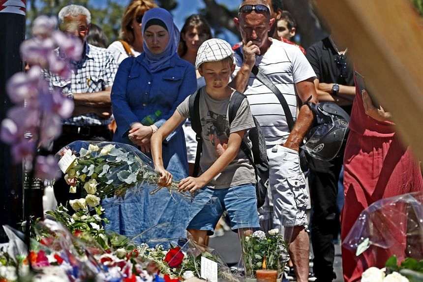 People gather in front of the memorial set on the Promenade des Anglais, on July 15, 2016, where the truck crashed into the crowd during the Bastille Day celebrations, in Nice, France.