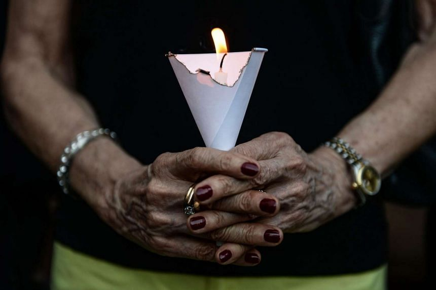 A member of the French community holds a candle during a vigil in Bangkok, on July 15, 2016.