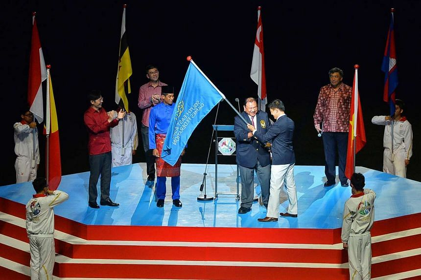 Tunku Imran, president of the Olympic Council of Malaysia, receives the SEA Games Federation flag at the closing ceremony of the 28th SEA Games, on June 16, 2015.