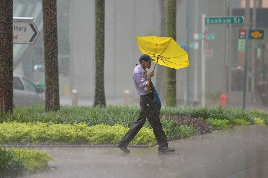 A man contending with the heavy downpour at Raffles Place on June 17, 2016.