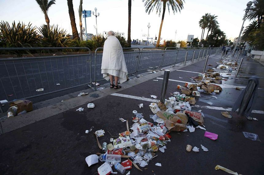 A man walks through debris scattered on the street the day after a truck ran into a crowd at high speed killing scores celebrating Bastille Day in Nice on July 15, 2016.