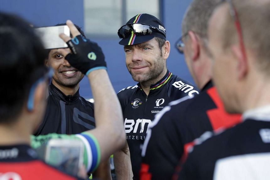 Former Tour de France winner Cadel Evans takes photos with cyclists from the local community after a ride in Seletar, on July 15, 2016.