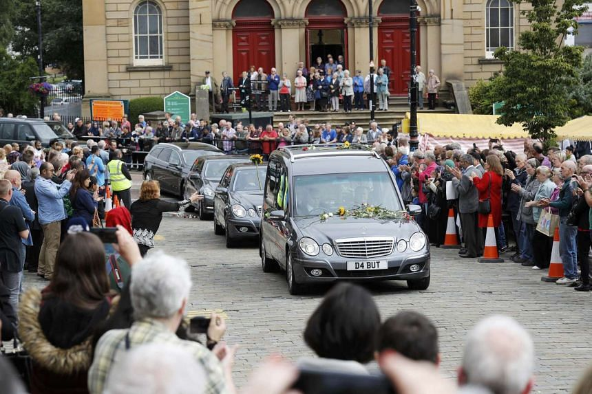 A woman throws a flower at the hearse carrying murdered MP Jo Cox as people line the road to watch her funeral cortege pass through Batlley, on July 15, 2016.