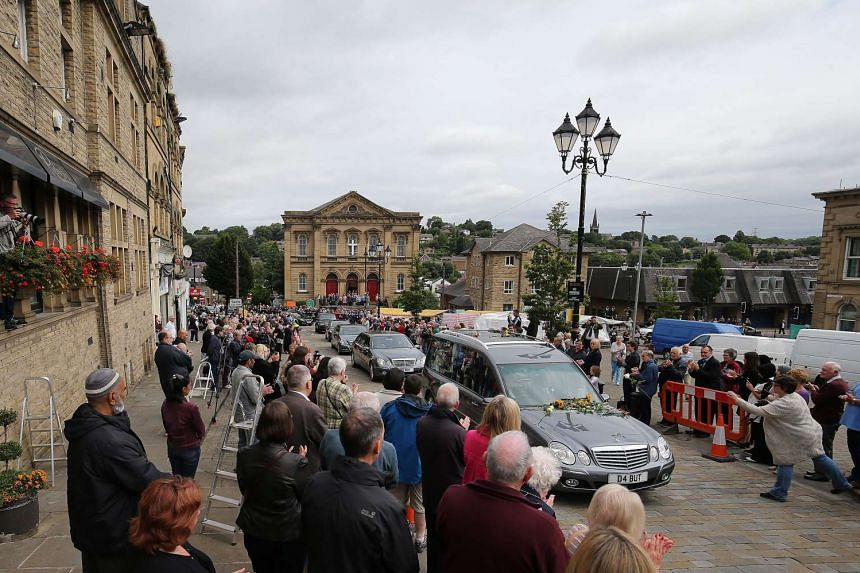 Mourners pay their respects as the funeral cortege of British MP Jo Cox passes through Batley, Britain on July 15, 2016.