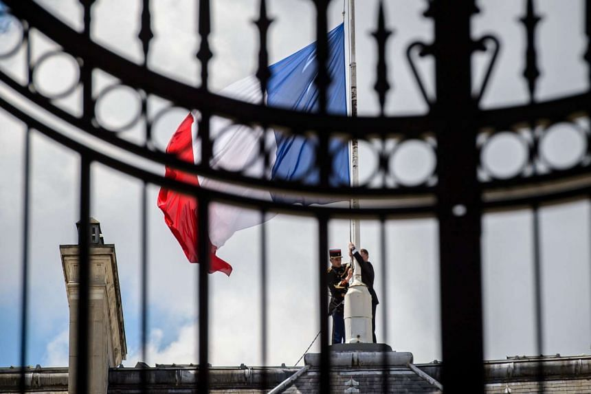A Republican Guard lowers the French national flag at half-mast at the Elysee Palace in Paris, France, on July 15, 2016.