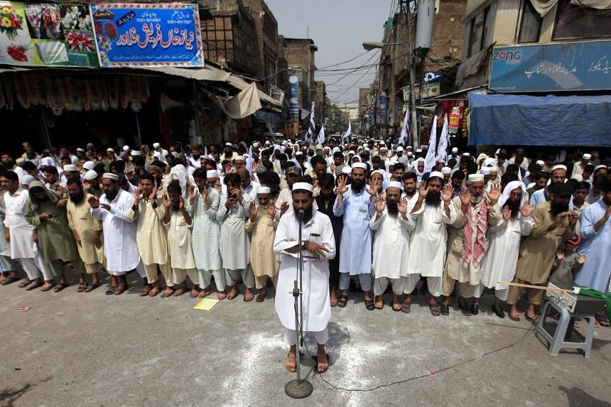 Supporters of banned Islamic charity Jamat-ud-Dawa attend absent funeral prayer of Kashmiri separatist leader Burhan Muzaffar Wani during a protest against India, in Peshawar on July 15, 2016.
