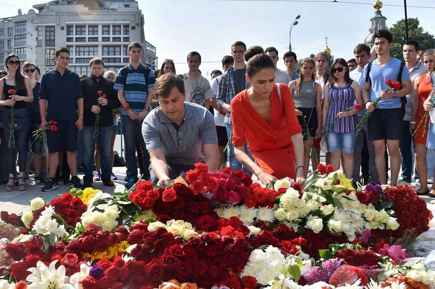 People lay flowers outside the French embassy in Moscow, on July 15, 2016, in tribute to the victims of the attack in Nice.