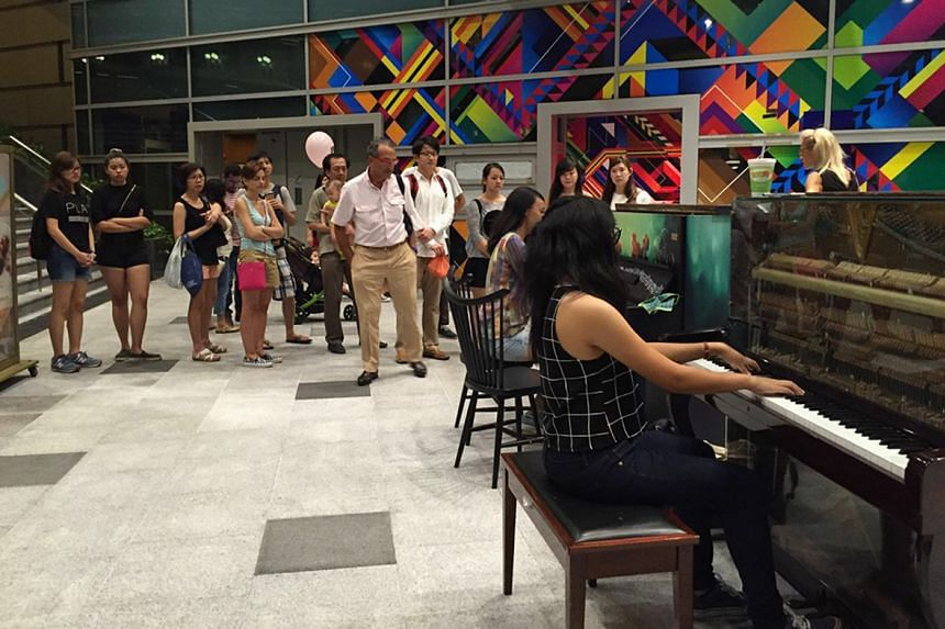 A crowd watching a performance on the pianos at One Fullerton.