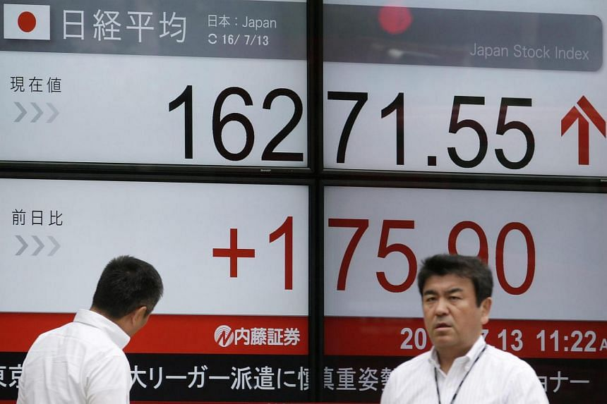 Businessmen walk past a display showing Tokyo's Nikkei Stock Average during the morning trade session in Tokyo, Japan on July 13, 2016.