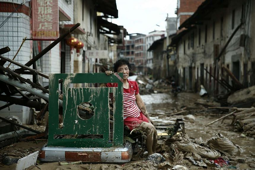 A woman sits on the ruins after typhoon Nepartak swept through Minqing county, Fujian province, on July 10, 2016.