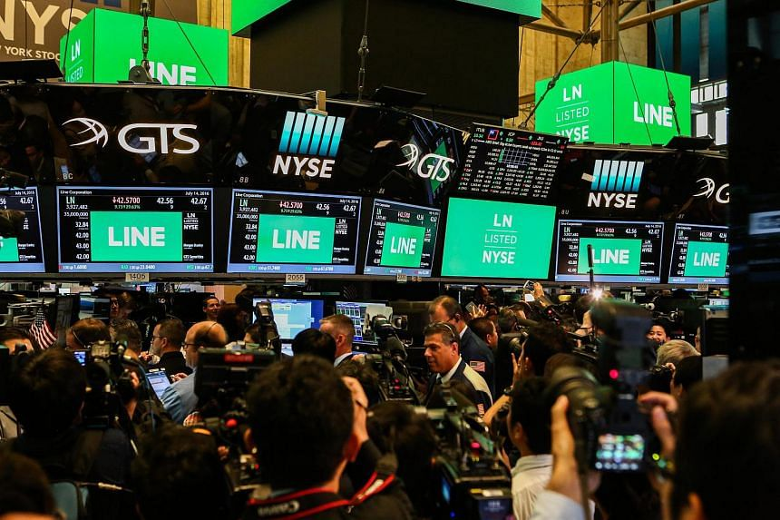 Traders and members of the media watch monitors with Line Corp. stock information on display at the NYSE in New York, US, on July 14.