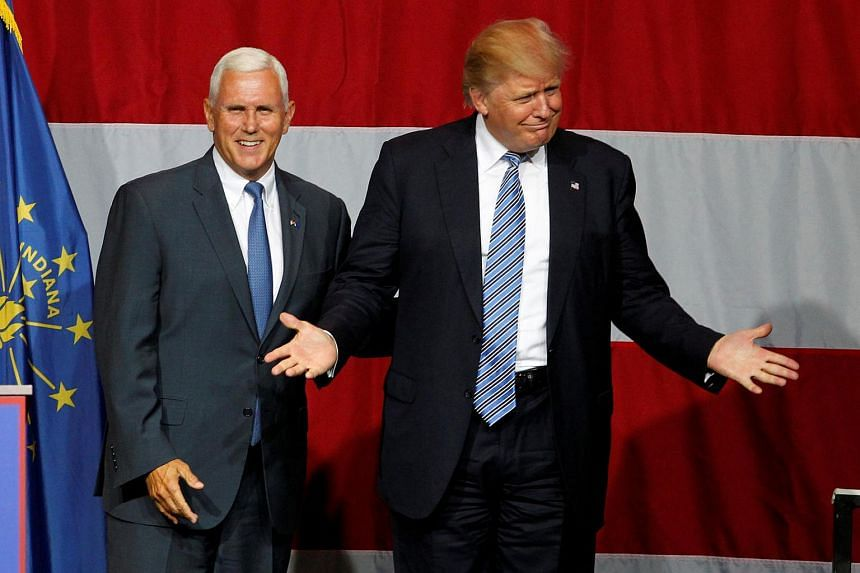 Republican US presidential candidate Donald Trump (right) and Indiana Governor Mike Pence wave to the crowd before addressing the crowd during a campaign stop at the Grand Park Events Center in Westfield, Indiana, July 12.