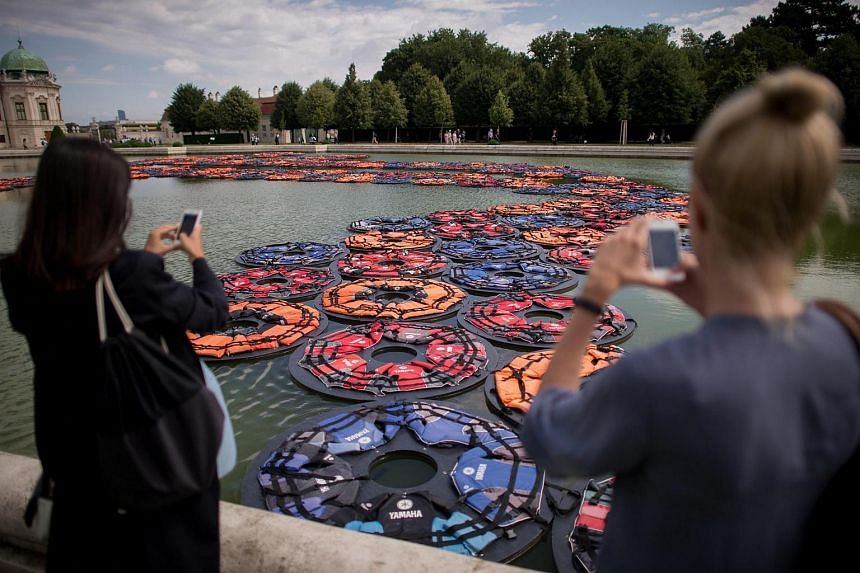 People take photographs of the artwork F Lotus by Chinese artist Ai Weiwei at the Belvedere Palace in Vienna, Austria, on July 13.