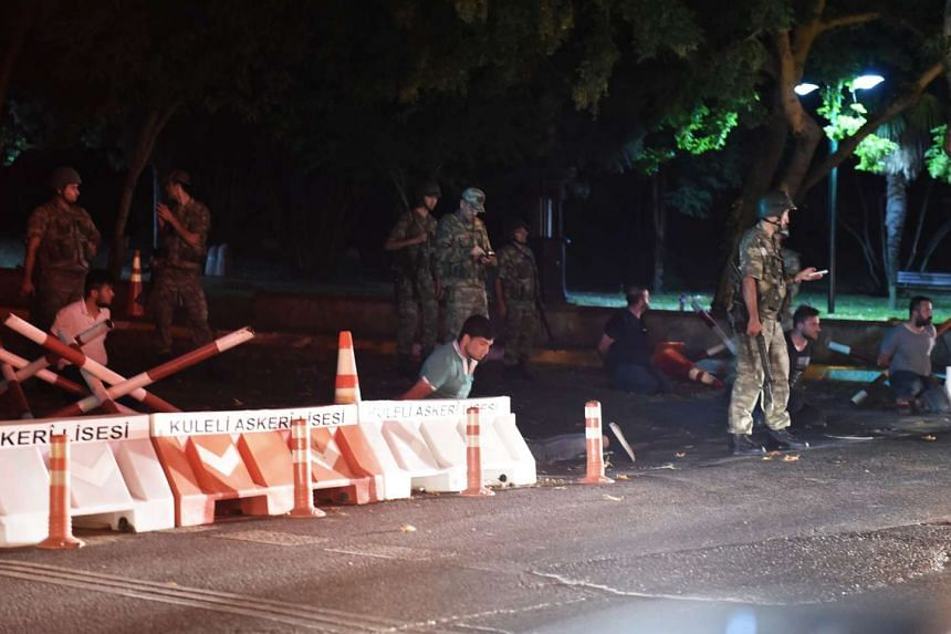 Turkish security officers detain unknown individuals on the side of the road on July 15, 2016 in Istanbul, during a security shutdown of the Bosphorus Bridge.