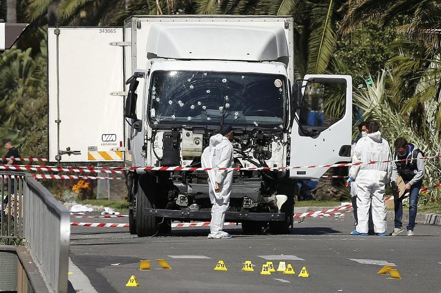Investigators at the scene yesterday after an assailant rammed his truck down a busy promenade filled with Bastille Day revellers. The entire country was stunned by the attack on the French Riviera city of Nice, which left scores dead.