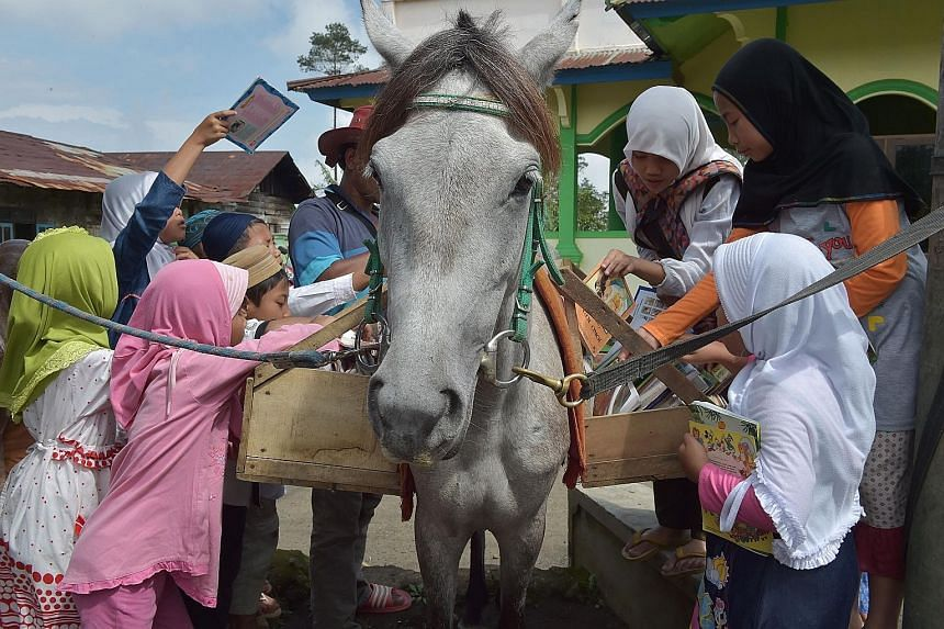 Indonesian children hunt for books from a mobile library on horseback as Mr Ridwan Sururi (partially hidden, with hat) compiles a book list for villagers in Serang, a quiet hamlet fringed by rice fields and a volcano on Indonesia's main island of Jav