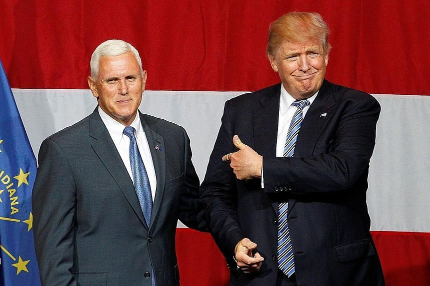 """Mr Donald Trump and Indiana Governor Mike Pence attending a rally in the state on Tuesday. The presumptive Republican presidential nominee has chosen Mr Pence as his running mate, a choice seen as """"safe"""" by analysts."""