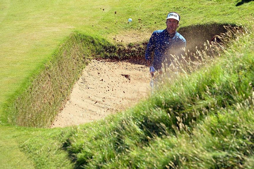 US golfer Bubba Watson blasting out of the Coffin Bunker at the side of the eighth hole at Royal Troon, on his way to a triple-bogey six. The Postage Stamp is one of the most unforgiving par threes.