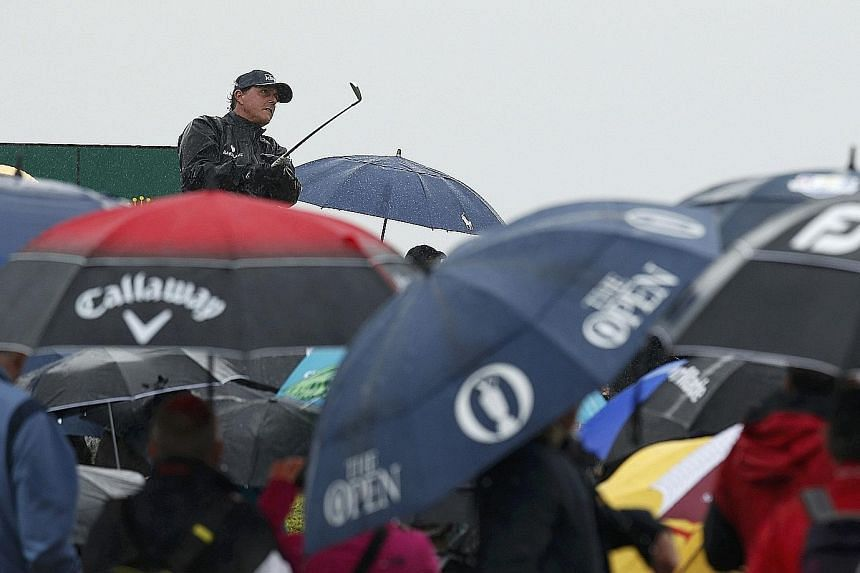 After his scintillating 63 in warm, sunny conditions on the opening day, Phil Mickelson of the United States watches his tee shot on the 16th hole as blustery, wet weather took hold at Royal Troon, Scotland yesterday.