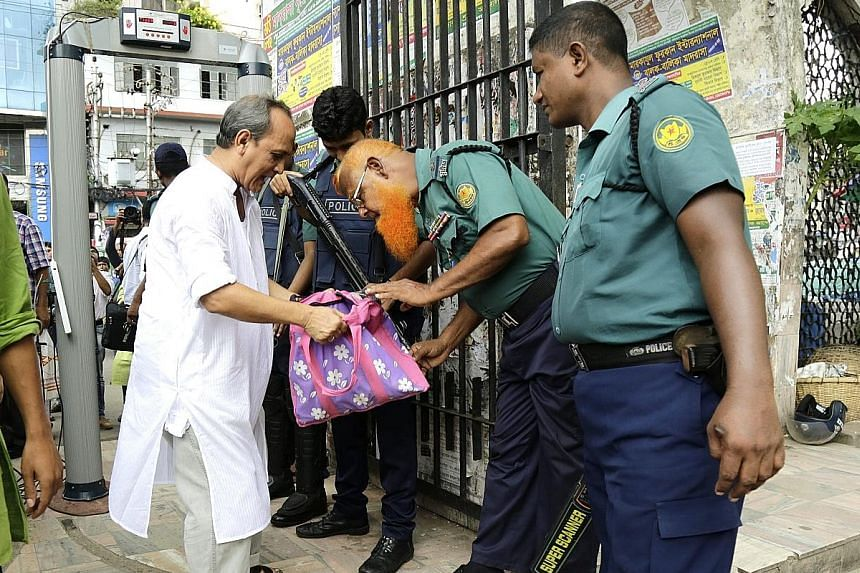 Security officials conducting checks at the entrance of the national mosque in Dhaka yesterday. Bangladesh has stepped up its campaign to combat Islamist extremism after a deadly cafe siege.