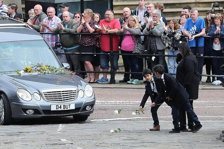 Mourners paying their respects as the funeral cortege of British MP Jo Cox passes through Batley, Britain, yesterday. Mrs Cox was murdered on June 16 while she was on her way to meet her constituents.