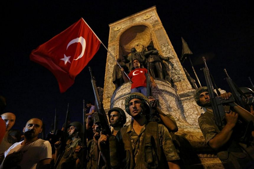 Turkish military stand guard near the the Taksim Square as people wave with Turkish flags in Istanbul, Turkey.