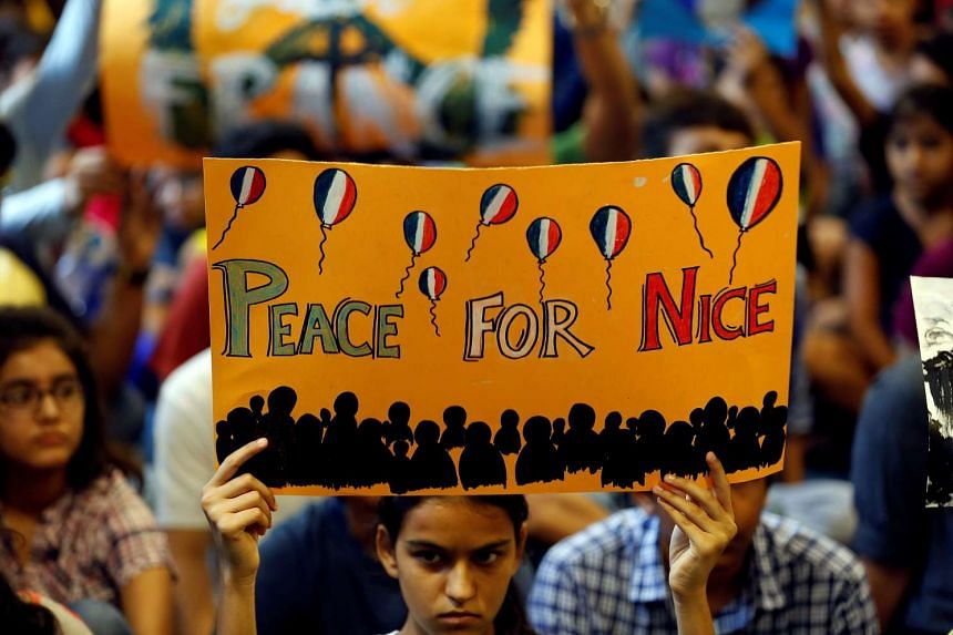 A girl holds up a placard during a prayer meet to show solidarity with the victims of the Bastille Day truck attack in Nice on July 15, 2016.