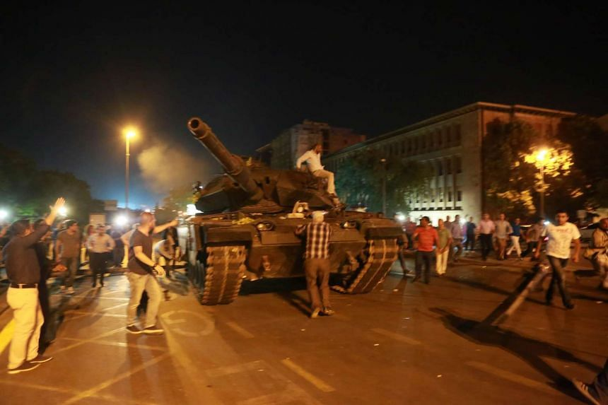People try to take over a tank in Ankara, Turkey during a protest agaist military coup on July 16, 2016.