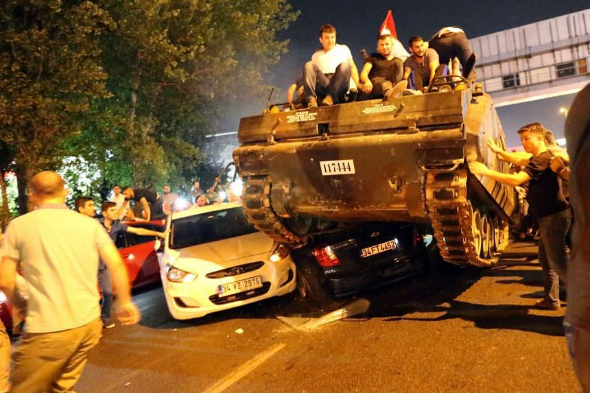 People on a tank run over cars on a road in Istanbul, Turkey, July 16, 2016.