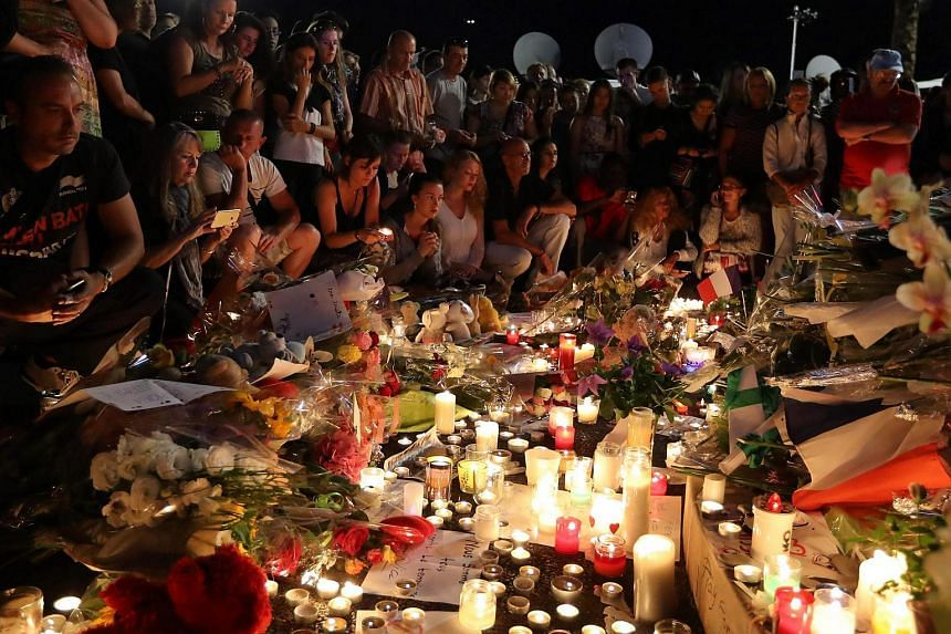 Members of the public lay flowers and light candles at a make-shift memorial site for victims of the Bastille Day attack, on July 15.