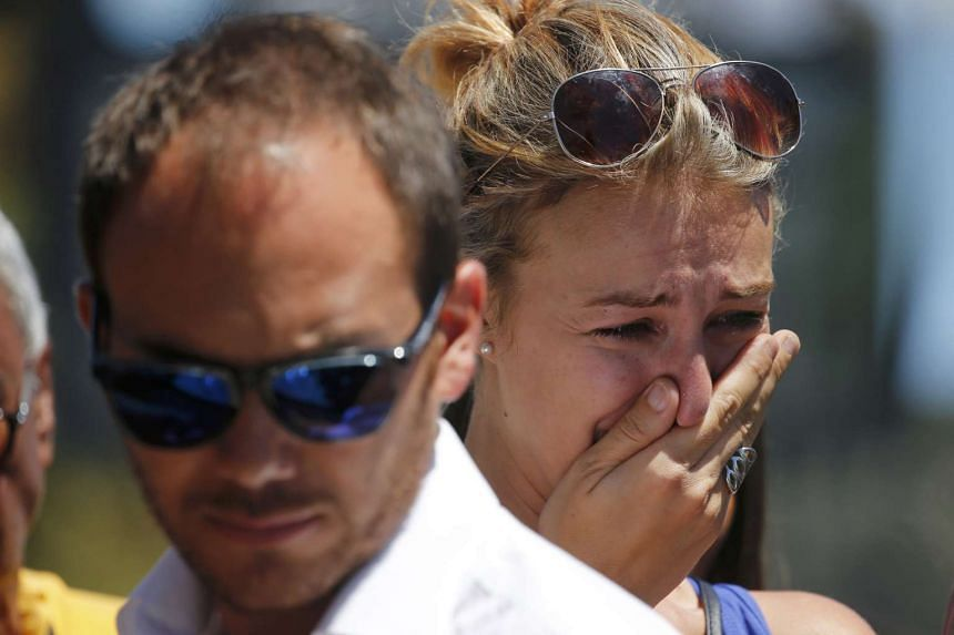 People react near the scene the day after the attack, on July 15, 2016.