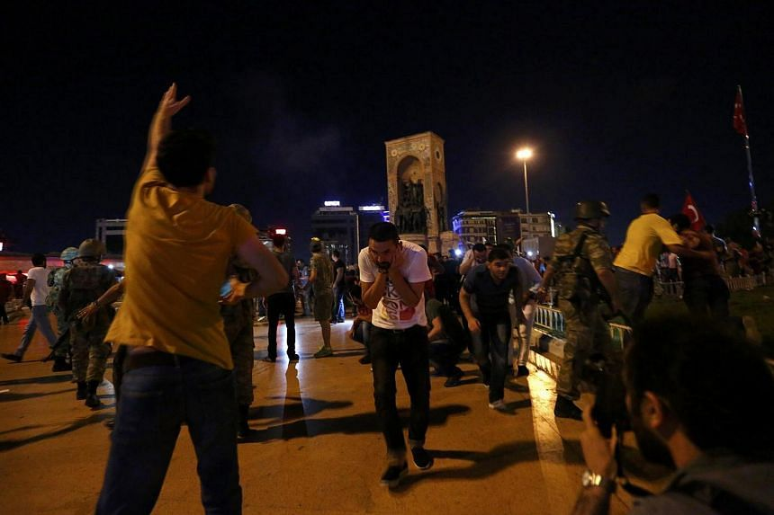 Shots are fired in the air to disperse supporters of Turkish President Tayyip Erdogan at the Taksim Square in Istanbul, Turkey, on July 16.