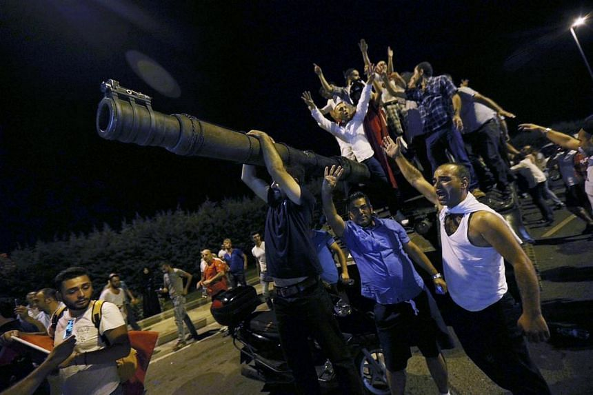 People stand on a Turkish army tank at Ataturk airport in Istanbul, Turkey on July 16.