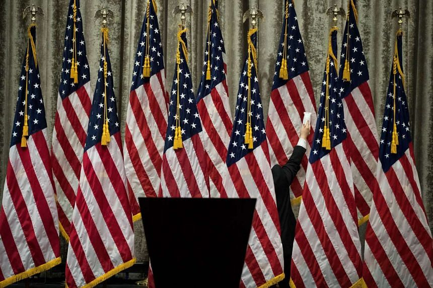 A campaign staffer steams the American flags before Republican presidential candidate Donald Trump and vice presidential running mate Mike Pence appeared together at the Hilton Midtown Hotel on July 16 in New York City.
