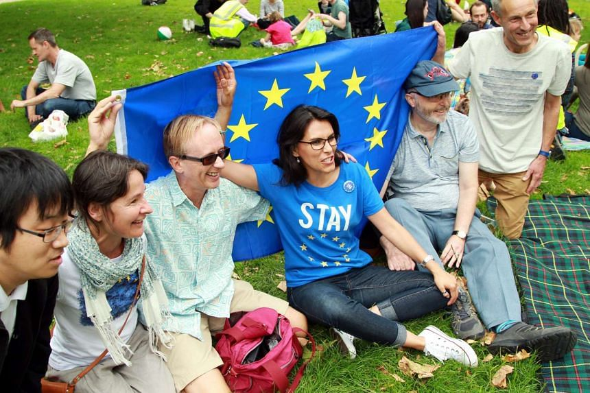 "People who are part of a crowd enjoying ""A Picnic to discuss Brexit"" in London on July 9, 2016."
