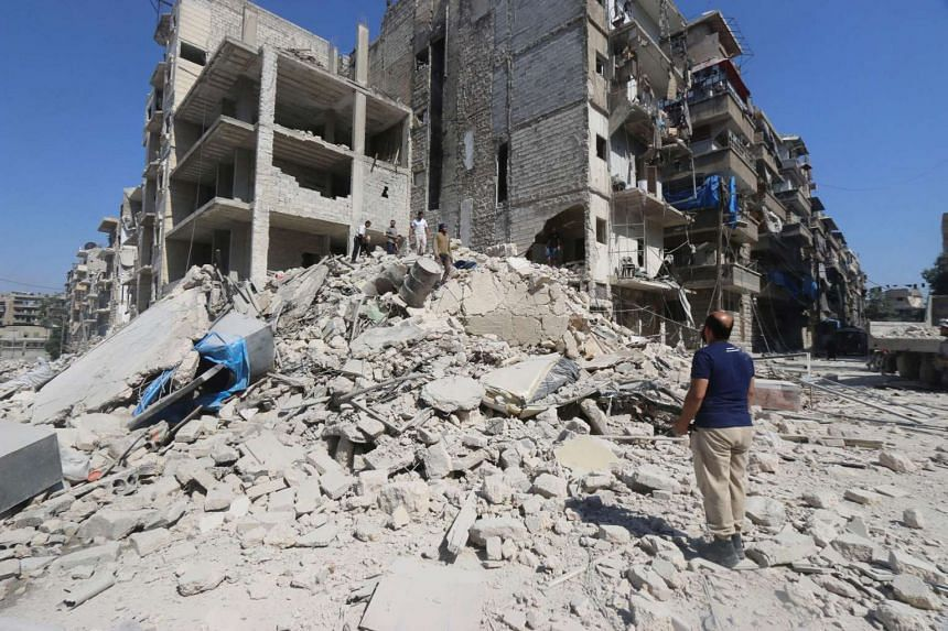 Men look for survivors amid rubble of damaged buildings after an airstrike on Aleppo's rebel held al-Maadi district on July 16, 2016.