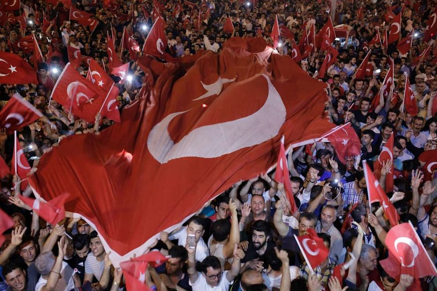 People hold Turkish flags in Taksim square in Istanbul on July 16, 2016 during a demonstration in support of the Turkish president.